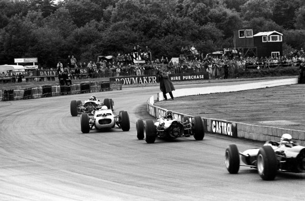 Race winner Jim Clark (GBR) Lotus 33 leads on the first lap from race retiree Richie Ginther (USA) Honda RA272, second placed Graham Hill (GBR) BRM P261 and Jackie Stewart (GBR) BRM P261 who finished fifth. British Grand Prix, Silverstone, 10 July 1965.