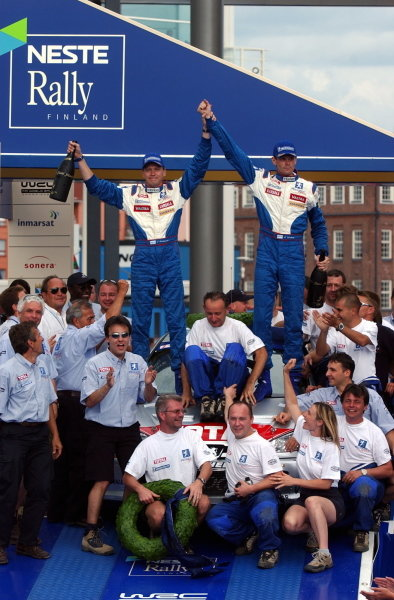 Rally winner Marcus Gronholm (FIN) and team mate Timo Rautiainen (FIN) Peugeot 206 WRC celebrate on the podium.