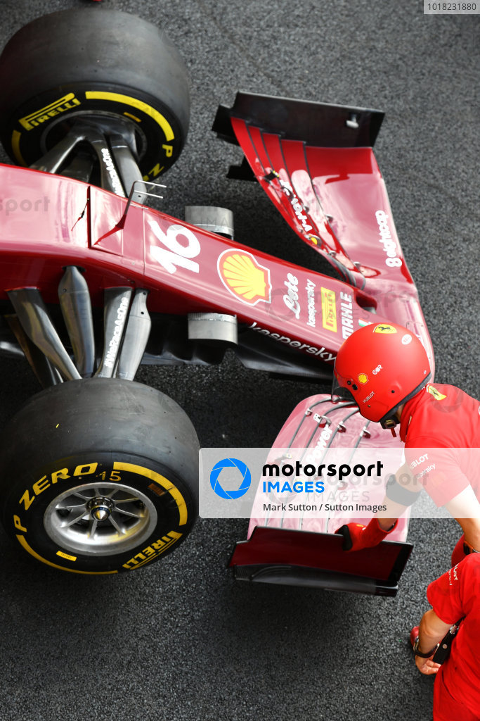 A Ferrari team member inspects a front wing on the Charles Leclerc Ferrari SF1000