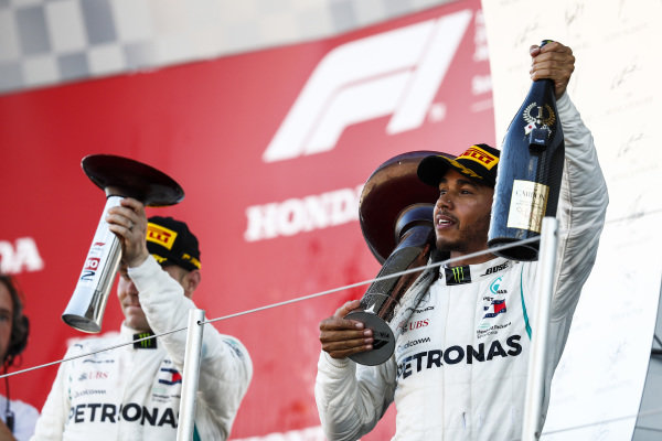 Valtteri Bottas, Mercedes AMG F1, 2nd position, and Lewis Hamilton, Mercedes AMG F1, 1st position, with their trophies on the podium