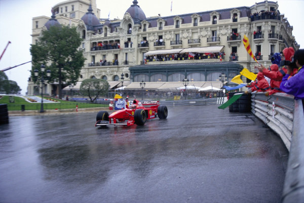 Michael Schumacher, Ferrari F310B, celebrates victory as marshals at Casino Square wave their flags in salute.