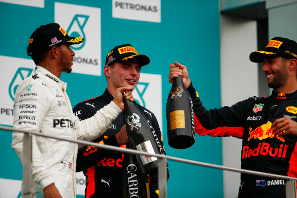 Sepang International Circuit, Sepang, Malaysia. Sunday 01 October 2017. Lewis Hamilton, Mercedes AMG, and Daniel Ricciardo, Red Bull Racing, toast winner Max Verstappen, Red Bull Racing, with champagne on the podium. World Copyright: Andy Hone/LAT Images  ref: Digital Image _ONY5365