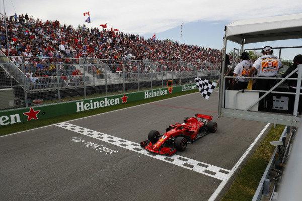 Sebastian Vettel, Ferrari SF71H, takes the chequered flag at the finish.