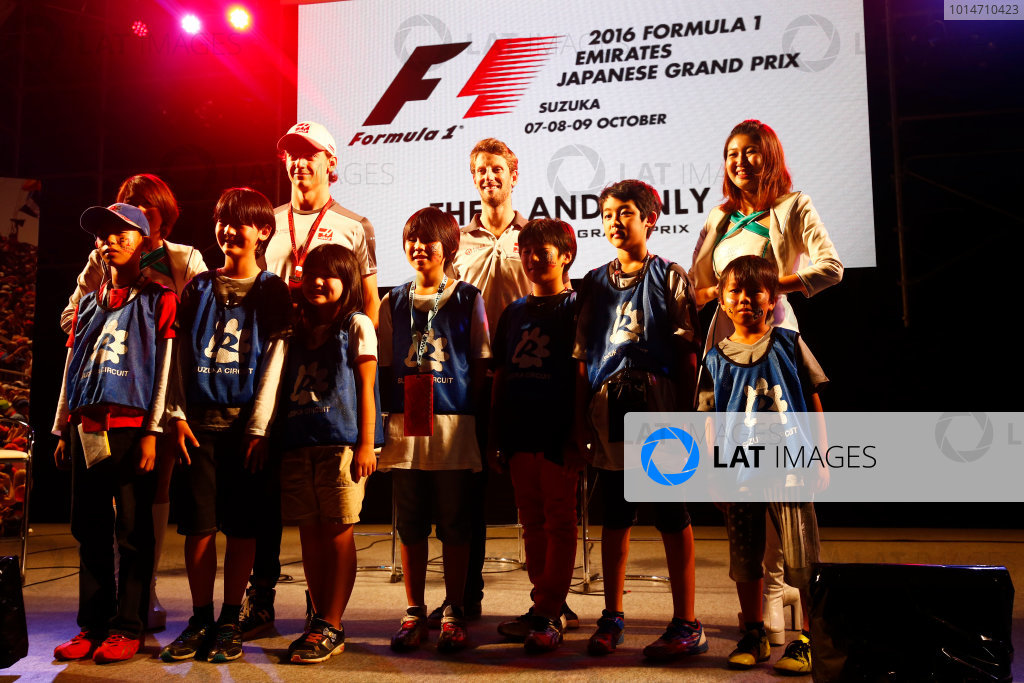 Suzuka Circuit, Japan. Saturday 08 October 2016. Esteban Gutierrez, Haas F1, Romain Grosjean, Haas F1, and children at a fan event. World Copyright: Andy Hone/LAT Photographic ref: Digital Image _ONZ4823