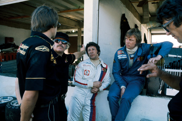 Interlagos, Brazil. 25 January 1976. Ronnie Peterson (Lotus 77-Ford), retired and Mario Andretti (Lotus 77-Ford), retired, listern to Colin Chapman after Mario had crashed and taken Peterson out as well, portrait.  World Copyright: LAT Photographic. Ref: 76BRA26