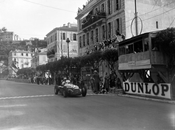Juan Manuel Fangio, Alfa Romeo 158, raises his arm in triumph as he crosses the line and takes the chequered flag.