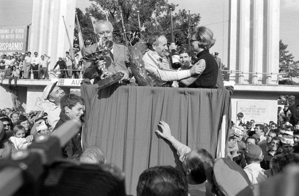 John Surtees, 1st position, celebrates on the podium.