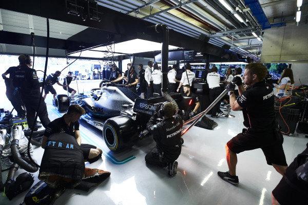 Mechanics make final preparations to the car of Valtteri Bottas, Mercedes AMG W10, in the garage