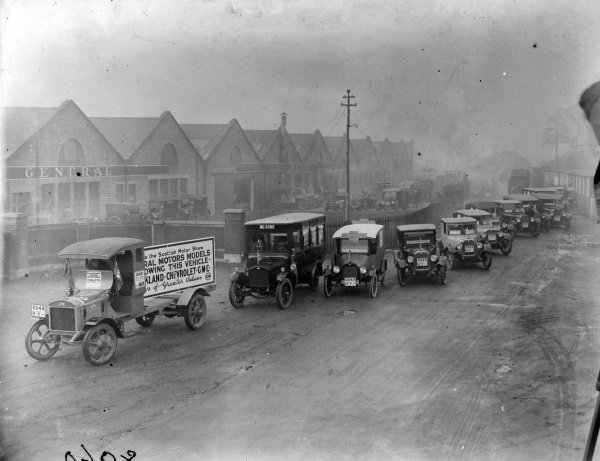 Lorry leading convoy of cars including Buick, Oakland, Chevrolet and GMC from the General Motors factory to the Scottish Motor Show