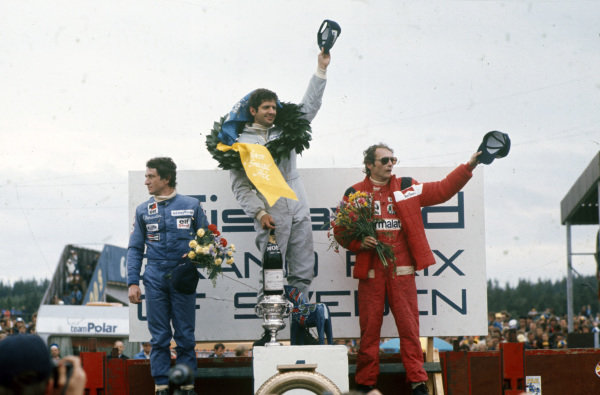 Jody Scheckter celebrates victory on the podium with teammate and Patrick Depailler, 2nd position and Niki Lauda, 3rd position.