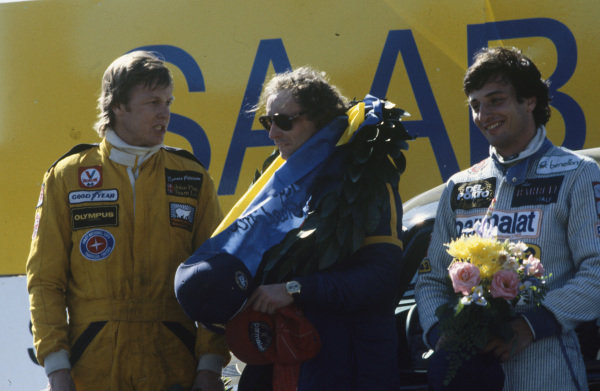 Winner Niki Lauda on the podium with Riccardo Patrese, 2nd position, and Ronnie Peterson, 3rd position.