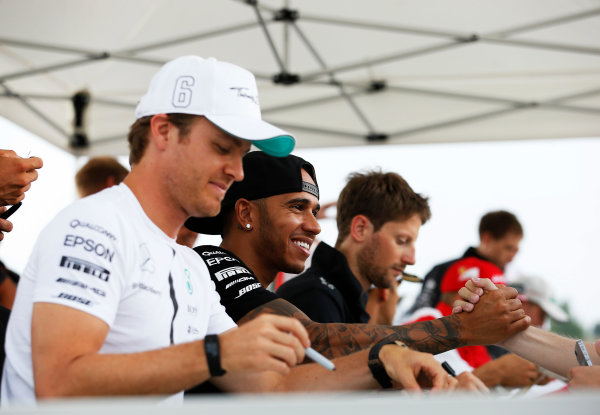 Hungaroring, Budapest, Hungary. Thursday 23 July 2015. Nico Rosberg, Mercedes AMG, Lewis Hamilton, Mercedes AMG, and Romain Grosjean, Lotus F1, sign autographs for fans. World Copyright: Charles Coates/LAT Photographic ref: Digital Image _J5R0509