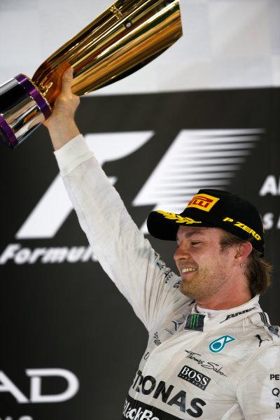 Yas Marina Circuit, Abu Dhabi, United Arab Emirates. Sunday 29 November 2015. Nico Rosberg, Mercedes AMG, 1st Position, lifts his trophy on the podium. World Copyright: Charles Coates/LAT Photographic ref: Digital Image _99O2675