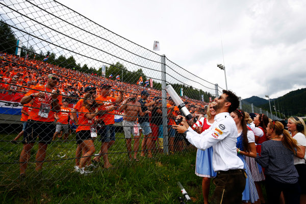 Red Bull Ring, Spielberg, Austria. Sunday 09 July 2017. Daniel Ricciardo, Red Bull Racing, shoots T-shirts into a crowd of largely Dutch fans, as Austrian promotional girls look on. World Copyright: Andy Hone/LAT Images ref: Digital Image _ONY2511