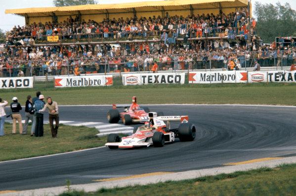 1974 Belgian Grand Prix.Nivelles-Baulers, Belgium. 12 May 1974.Emerson Fittipaldi (McLaren M23-Ford) leads Niki Lauda (Ferrari).World Copyright: LAT Photographicref: 35mm Transparency Image