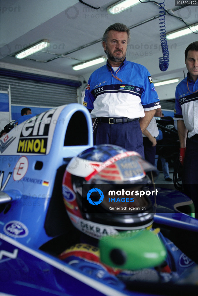 Michael Schumacher's manager Willi Weber standing behind his driver.