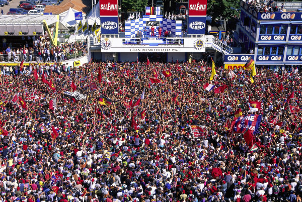 Fans gather in front of the podium where Michael Schumacher celebrates victory with Jean Alesi, 2nd position, and Mika Hakkinen, 3rd position.