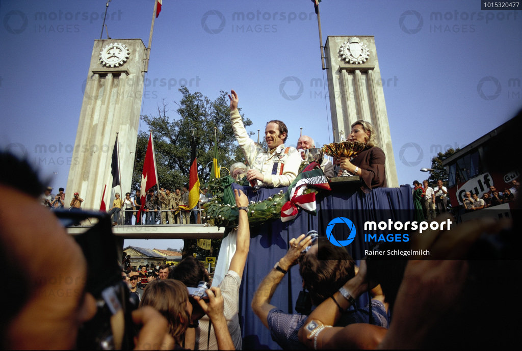 Peter Gethin celebrates victory on the podium. Behind him is BRM team boss Louis Stanley Lorenzo Bandini's wife Margherita Freddi on the right.