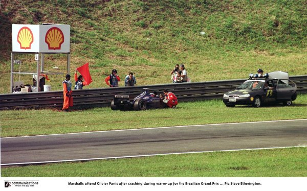 1998 Brazilian Grand Prix.Interlagos, Sao Paulo, Brazil.27-29 March 1998.Marshals attend Olivier Panis (Prost AP01 Peugeot) after he crashed during the warm-up.World Copyright - Steve Etherington/LAT Photographic