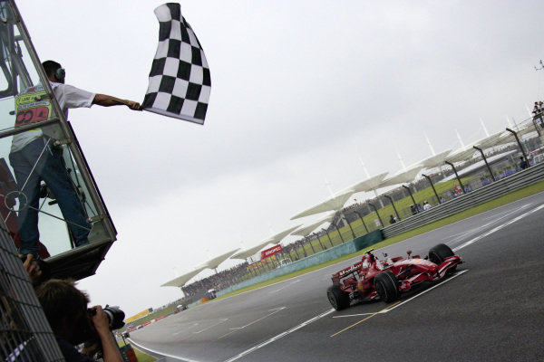 Kimi Räikkönen, Ferrari F2007 raises his fists in celebration as he takes the chequered flag for victory.