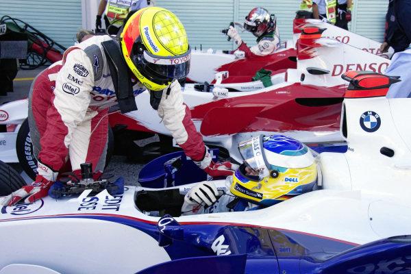 Ralf Schumacher chats to Nick Heidfeld still sat in his cockpit in parc fermé.