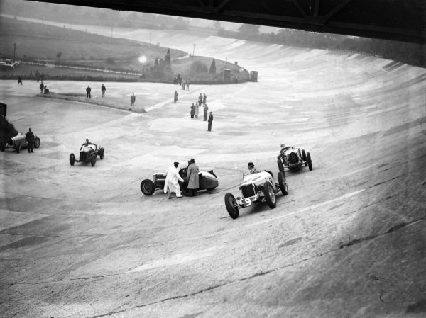 Raymond Mays, Riley, looks back at officials trying to move Malcolm Campbell's Sunbeam Tiger.  Piero Taruffi, Bugatti T51, follows behind Mays, while Brian Lewis, Alfa Romeo Monza, stays low to avoid the abandoned car.
