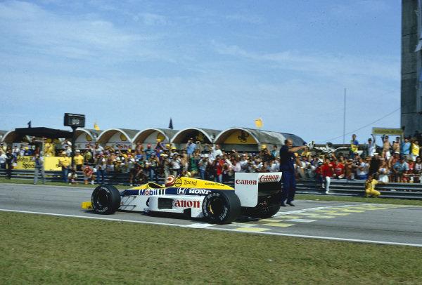 1986 Brazilian Grand Prix.Jacarepagua, Rio de Janeiro, Brazil.21-23 March 1986.Nelson Piquet (Williams FW11 Honda) crosses the line and takes the chequered flag for 1st position.Ref-86 BRA 18.World Copyright - LAT Photographic
