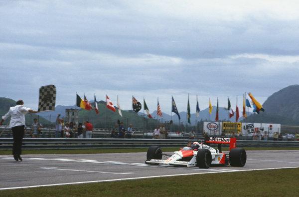 Jacarepagua, Rio de Janeiro, Brazil.1-3 April 1988.Alain Prost (McLaren MP4/4 Honda), 1st position, takes the chequered flag, action. World Copyright: LAT Photographic.Ref:  88BRA05.