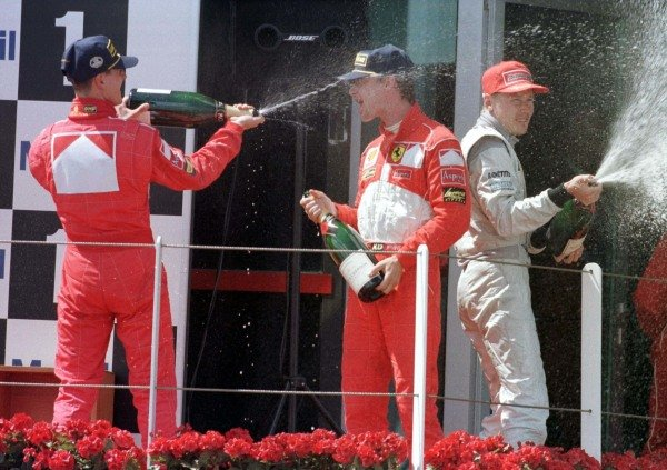 1998 French Grand Prix. Magny-Cours, Nevers, France. 26-28 June 1998. Michael Schumacher, Eddie Irvine (both Ferrari) and Mika Hakkinen (McLaren-Mercedes-Benz) celebrate finishing in 1st, 2nd and 3rd positions. World Copyright - Etherington/LAT Photographic