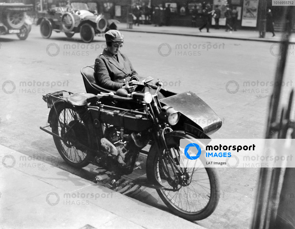 A Women's Royal Air Force driver reads a book while she waits in her motorcycle sidecar for her passenger.