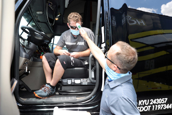 A driver for a team hauler has their temperature checked.  Copyright: Chris Graythen / Getty Images