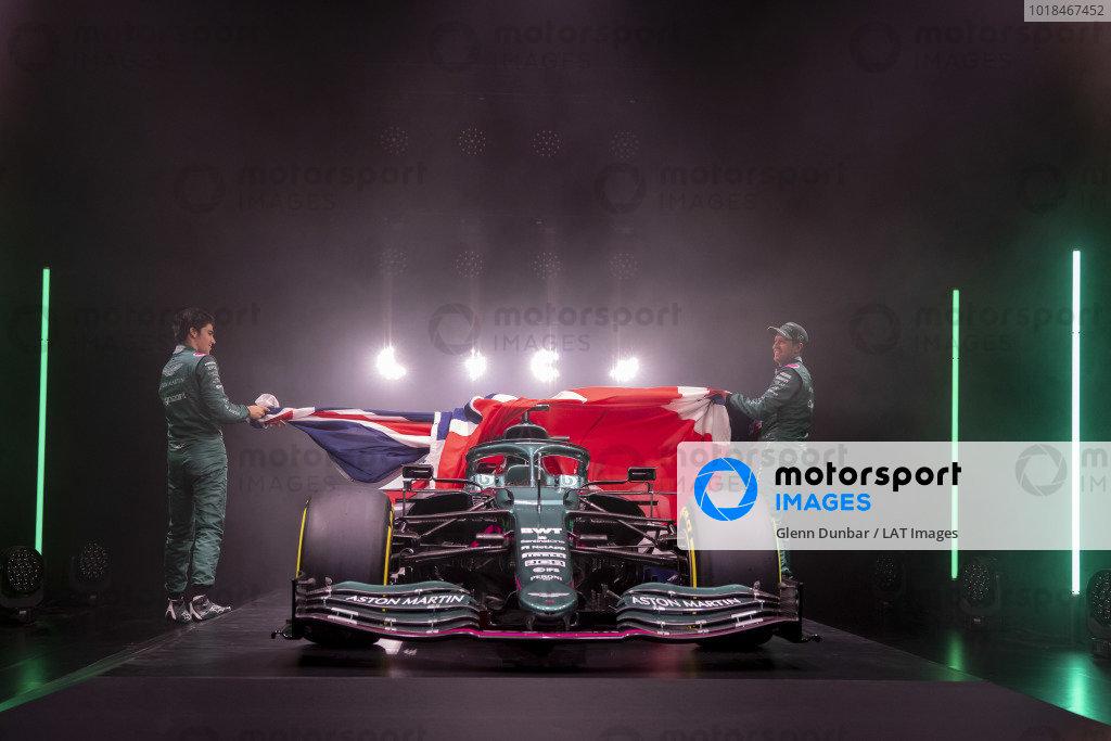 Lance Stroll, Aston Martin, and Sebastian Vettel, Aston Martin, lift the Union Jack to unveil the new Aston Martin AMR21