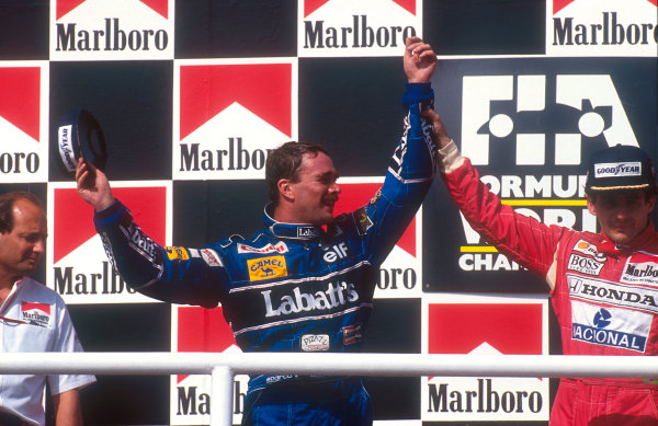 1992 Hungarian Grand Prix.Hungaroring, Budapest, Hungary.14-16 August 1992.Nigel Mansell (Williams Renault) celebrates 2nd position on the podium and winning the drivers World Championship. Ayrton Senna (McLaren Honda) 1st position also congratulates him. McLaren team boss Ron Dennis also stands to the left.Ref-92 HUN 11.World Copyright - LAT Photographic