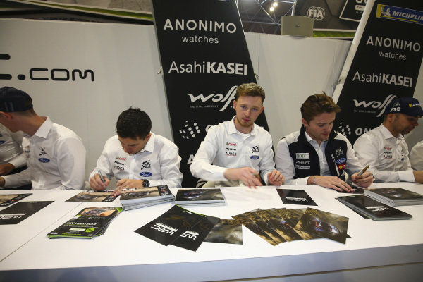 WRC drivers sign autographs.