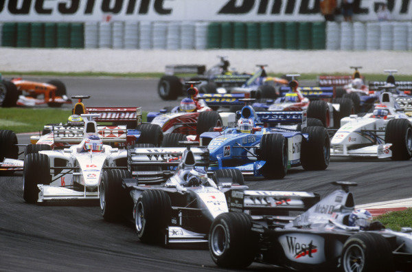 Sepang, Kuala Lumpur, Malaysia. 15-17 October 1999. The field streams through the first two corners at the start of the race. Action. Ref: 99MAL58. World Copyright - LAT Photographic