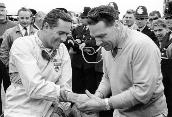1960 British Grand Prix. Silverstone, Great Britain. 14-16 July 1960. Jack Brabham (Cooper T53-Climax), 1st position, with team owner John Cooper. Portrait. World Copyright: LAT Photographic Ref: Autosport b&w print