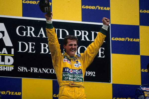 Spa-Francochamps, Belgium. 28-30 August 1992. Michael Schumacher (Benetton Ford) celebrates his maiden Grand Prix win on the podium. Ref: 92 BEL 10. World Copyright - LAT Photographic