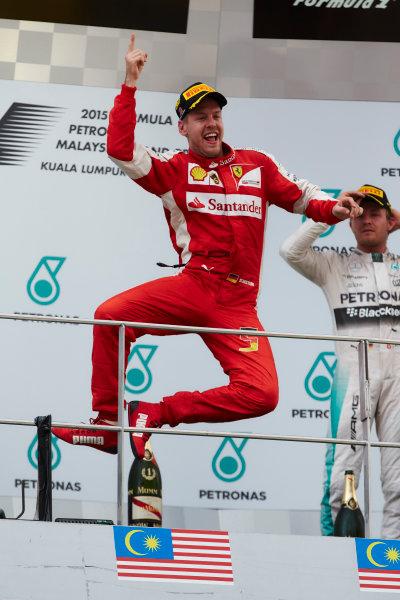 Sepang International Circuit, Sepang, Kuala Lumpur, Malaysia. Sunday 29 March 2015. Sebastian Vettel, Ferrari, 1st Position, leaps in celebration on the podium. World Copyright: Steve Etherington/LAT Photographic. ref: Digital Image SNE16343