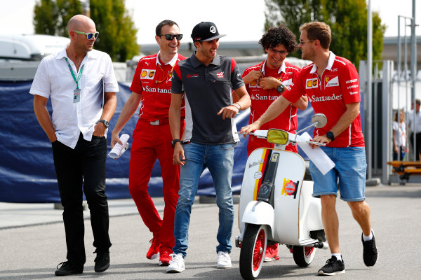Sebastian Vettel, Ferrari, meets Antonio Giovinazzi, Ferrari, as they arrive at the circuit.