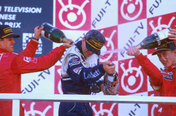 Suzuka, Japan.11-13 October 1996.Damon Hill (Williams Renault) 1st position, Michael Schumacher (Ferrari) 2nd position and Mika Hakkinen (McLaren Mercedes) 3rd position celebrate on the podium. Ref-96 JAP 08.World Copyright - LAT Photographic