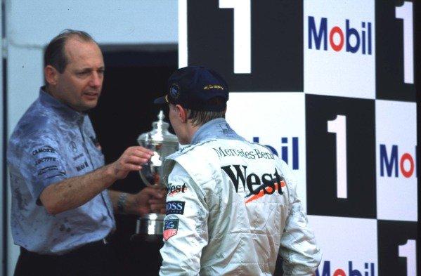 1997 European Grand Prix.Jerez, Spain.24-26 October 1997.Mika Hakkinen (McLaren Mercedes) celebrates his 1st position and maiden Grand Prix win on the podium, with team boss Ron Dennis.World Copyright - LAT Photographic