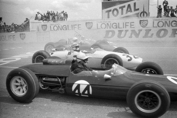 Jo Bonnier, Cooper T60 Climax, alongside Innes Ireland, BRP 1 BRM, at the start.