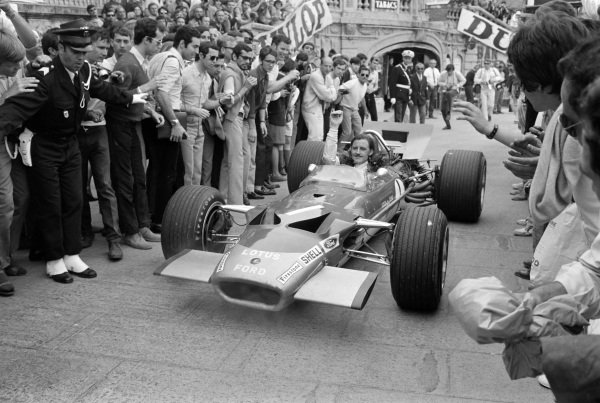 Graham Hill, Lotus 49B Ford, raises a hand to acknowledge the applause of spectators.