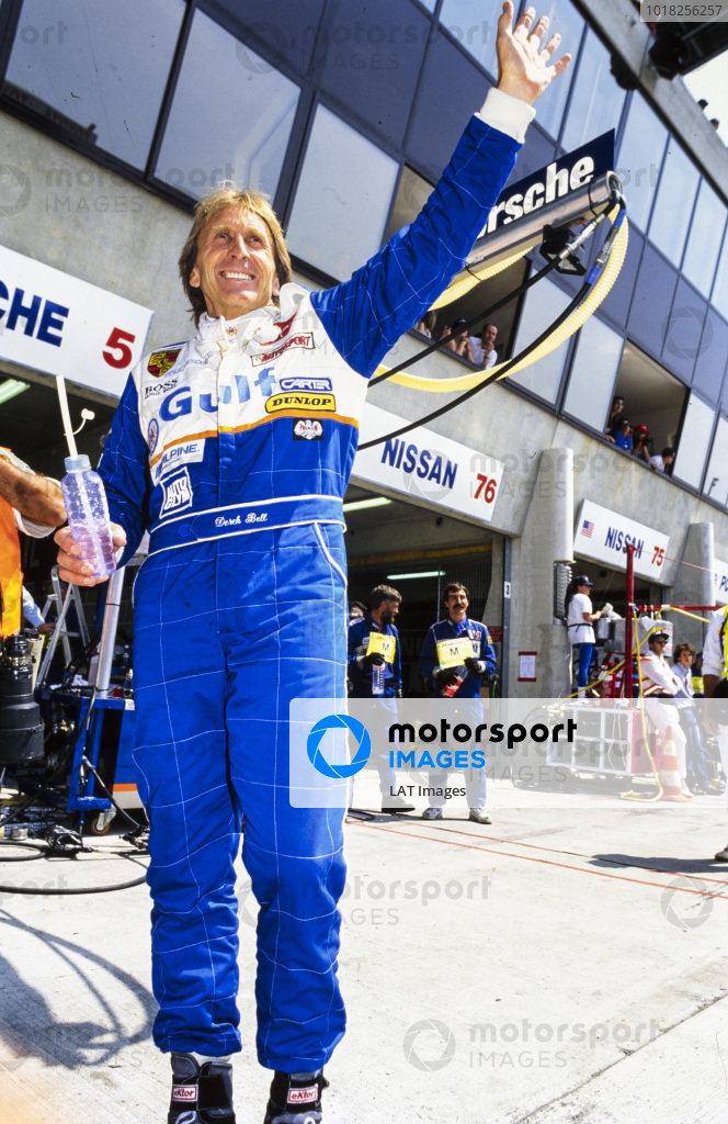 Derek Bell waves to the crowd in the pitlane.