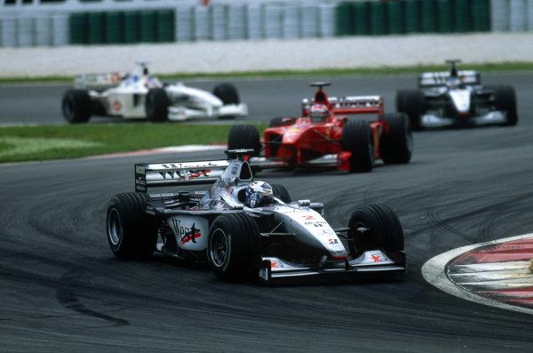 Sepang, Kuala Lumpur, Malaysia. 15-17 October 1999. David Coulthard (McLaren MP4/14 Mercedes) leads Michael Schumacher (Ferrari F399), Mika Hakkinen (McLaren MP4/14 Mercedes) and Rubens Barrichello (Stewart SF-3 Ford). Action. Ref: 99MAL09. World Copyright - LAT Photographic