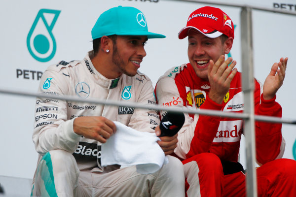Sepang International Circuit, Sepang, Kuala Lumpur, Malaysia. Sunday 29 March 2015. Lewis Hamilton, Mercedes AMG, 2nd Position, and Sebastian Vettel, Ferrari, 1st Position, talk on the podium. World Copyright: Andrew Hone/LAT Photographic. ref: Digital Image _ONZ0647