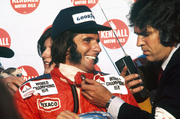 1974 United States Grand Prix East. Watkins Glen, New York, USA. 4th - 6th October 1974. Emerson Fittipaldi (McLaren M23-Ford), 4th position, portrait. New drivers world champion Emerson Fittipaldi celebrates taking his second world title.World Copyright: LAT Photographic. Ref: 74USA02.