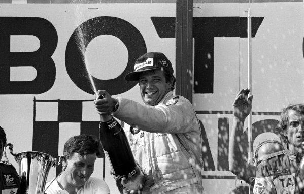 Elio de Angelis (ITA) Lotus celebrates his first Grand Prix victory on the podium. Austrian Grand Prix, Osterreichring, 15 August 1982.