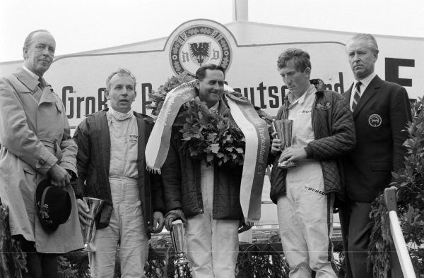 Race winner Jack Brabham on the podium with John Surtees, 2nd position, and Jochen Rindt, 3rd position.