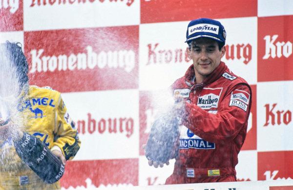 Ayrton Senna sprays champagne on the podium.